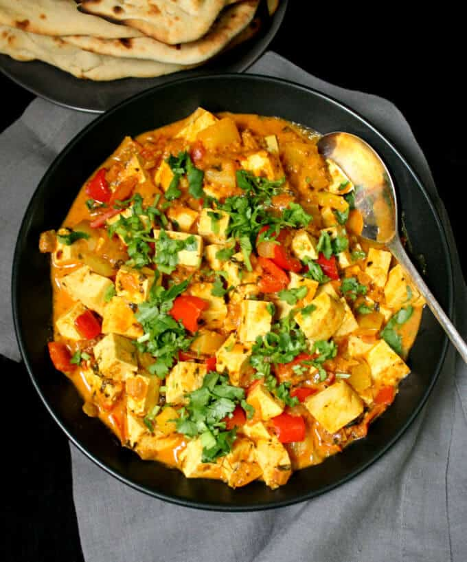 Photo of Instant Vegan Methi Malai Paneer in a black bowl with a spoon and naan on the side.