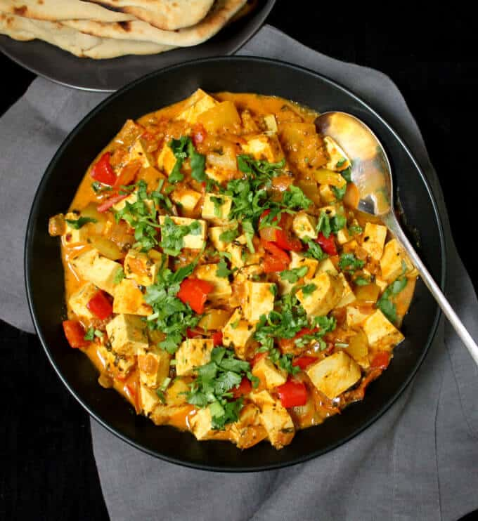 Overhead shot of Instant Methi Malai Paneer in a black bowl with a silver spoon.