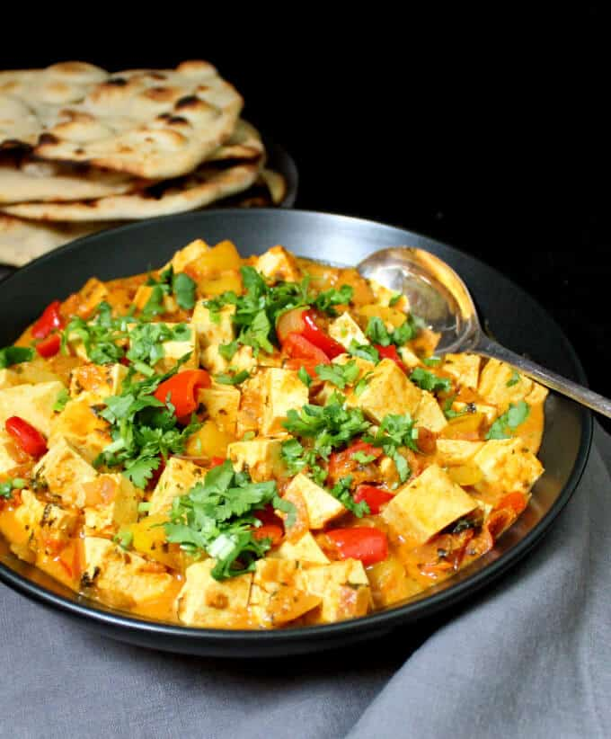 Photo of Instant Vegan Methi Malai Paneer in a black bowl with vegan naan served on the side.