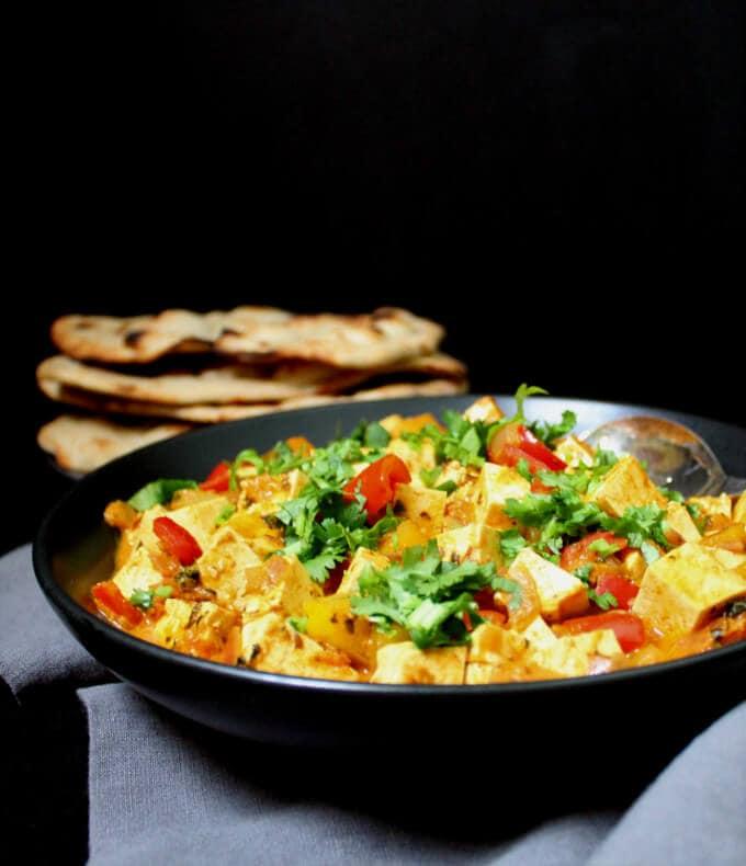 Instant Methi Malai Paneer Tofu in a black bowl with vegan naan on the side.