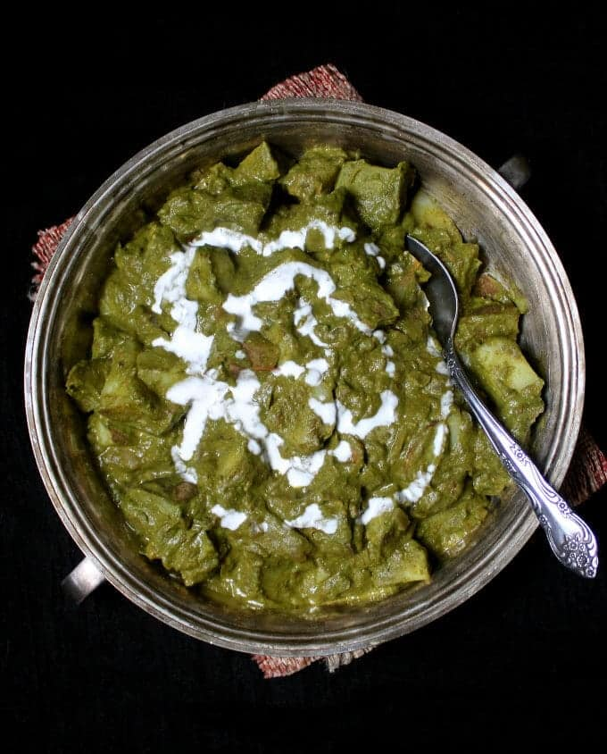 A delicious and healthy recipe for Aloo Palak, a spinach and potato curry, made in under 20 minutes with my basic tomato onion sauce. #vegan #indianfood #dinnerrecipe #spinach #potatoes HolyCowVegan.net