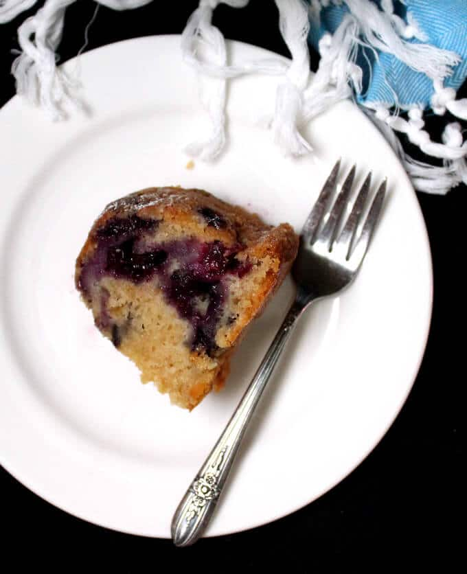 Photo of a slice of vegan blueberry buttermilk bundt cake on a white plate with a fork.