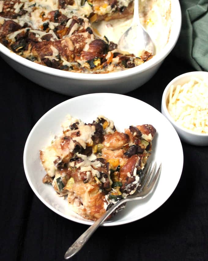 A Vegan Cheesy Croissant Casserole is the perfect dish for breakfast or brunch. It is golden, bubbling, cheesy and creamy, and scattered with delicious bits of croissants and vegan sausage. #vegan, #casserole, #soyfree, #croissant HolyCowVegan.net