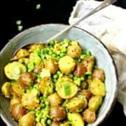 """Vegan Indian potato salad in an earthenware bowl with turmeric, green peas and scallions with inlay image that says """"vegan Indian style Potato Salad with Turmeric and Green Peas"""""""