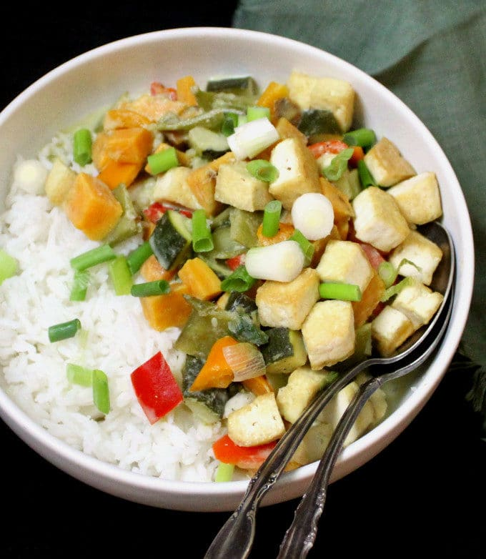 A bowl of rice with vegan Thai green curry with tofu and veggies