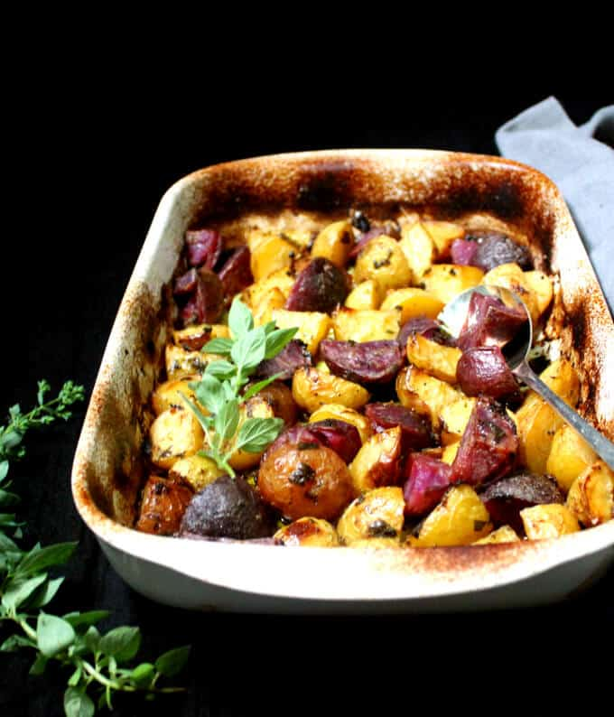 A white baking dish with colorful potatoes cooked in a lemony sauce with oregano in a Greek style