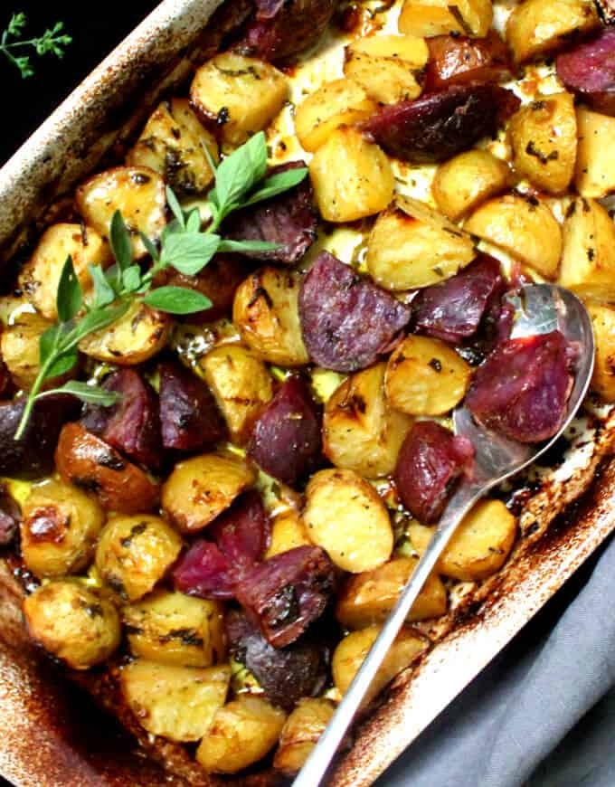 Overhead shot of a white baking dish with colorful lemony Greek style potatoes with a sprig or oregano and a silver spoon on a gray napkin