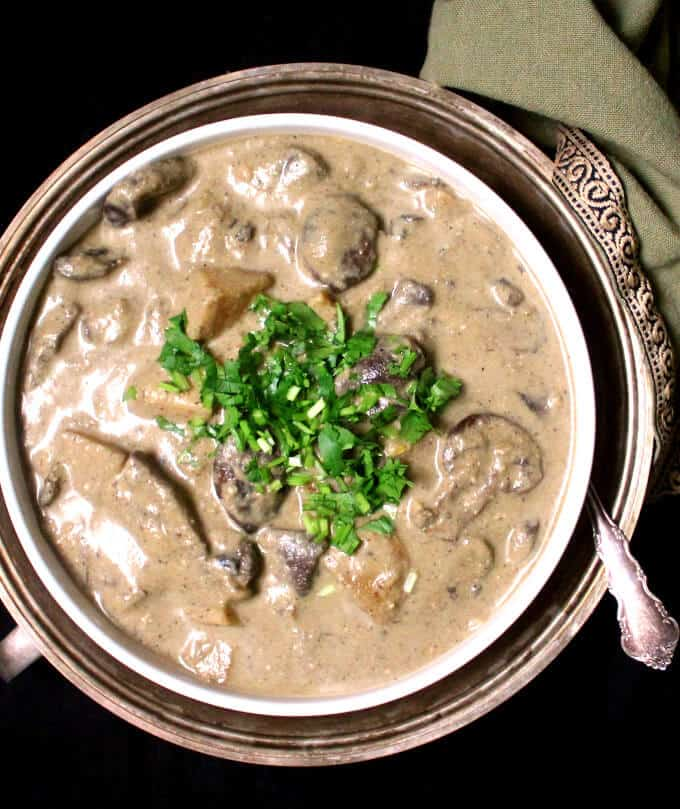 Top shot of Vegan Malaysian Mushroom Korma in a white bowl in silver serving dish with a green napkin.
