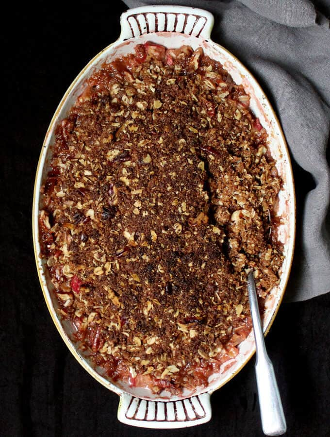 A vegan rhubarb crisp that is easy as pie to make. A gooey, jelly-like, tart rhubarb filling is topped with a golden, delicious, oat and nut crisp. Can be a gluten-free recipe. Perfect for breakfast or dessert.