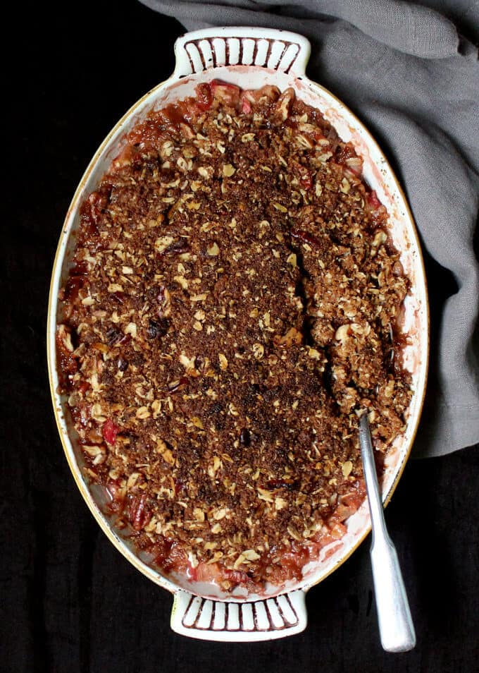 Overhead photo of a vegan rhubarb crisp topped with a crispy oat and nut streusel in a yellow and white baking dish.