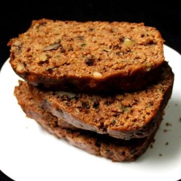 Slices of vegan zucchini bread stacked on a white plate.