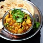 A close up of a copper and steel Indian handi bowl with aloo matar and chapatis