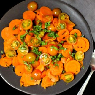 A partial top shot of a plate of curried carrot salad with cherry tomatoes and cilantro sprinkled on top