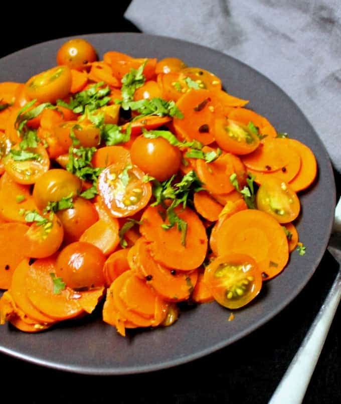A partial front shot of a plate of curried carrot salad with cherry tomatoes and Indian spices and cilantro