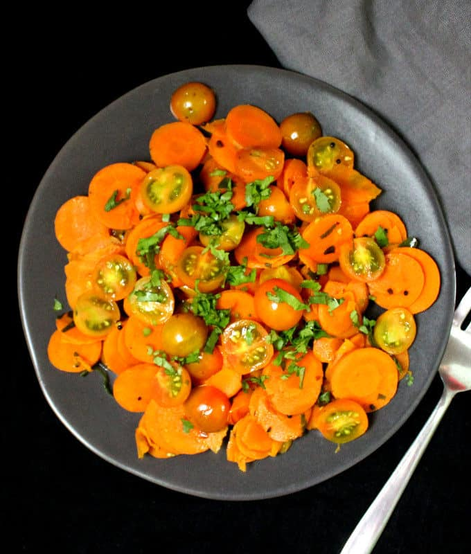 A gray plate with curried carrot salad with cherry tomatoes and a tempering of Indian spices and cilantro, against a black background with a fork and a gray napkin