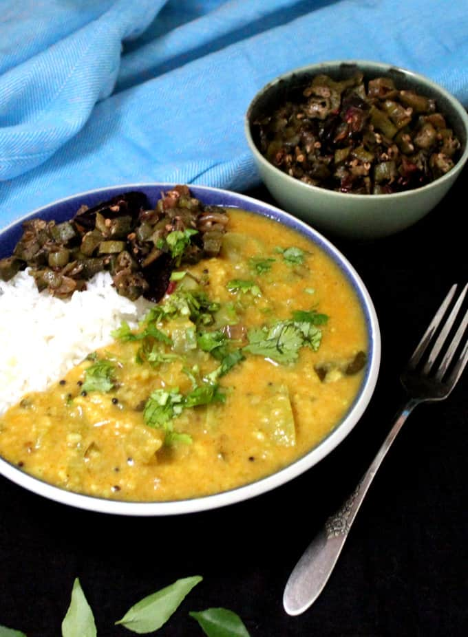 A partial shot of a south Indian green tomato dal in a bowl with rice and okra sabzi