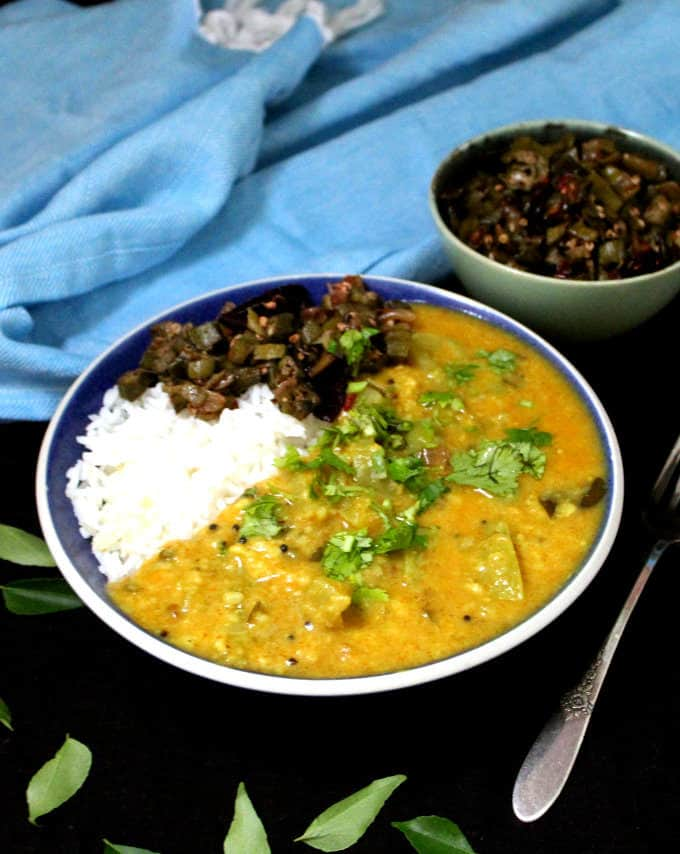 A front shot of the green tomato dal in a bowl with rice and okra subzi and a blue napkin behind.