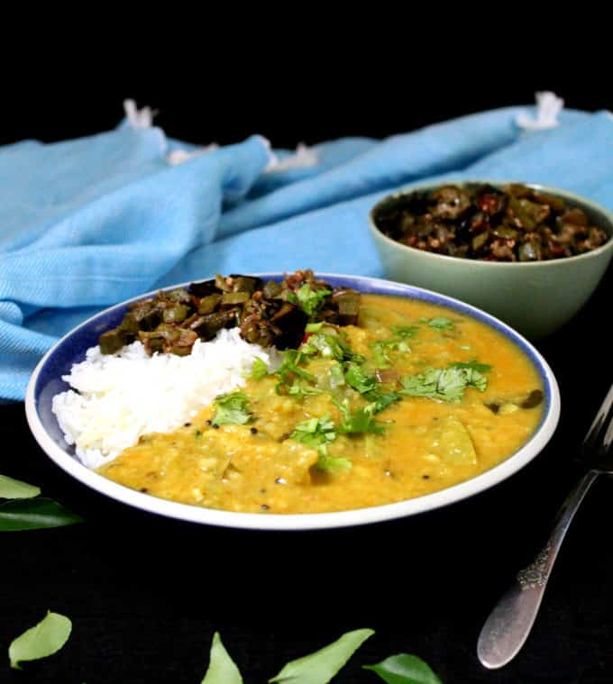 A frontal shot of a blue bowl with green tomato dal and okra subzi with rice. Curry leaves are strewn in the foreground and there's a blue napkin with a white fringe in the back.
