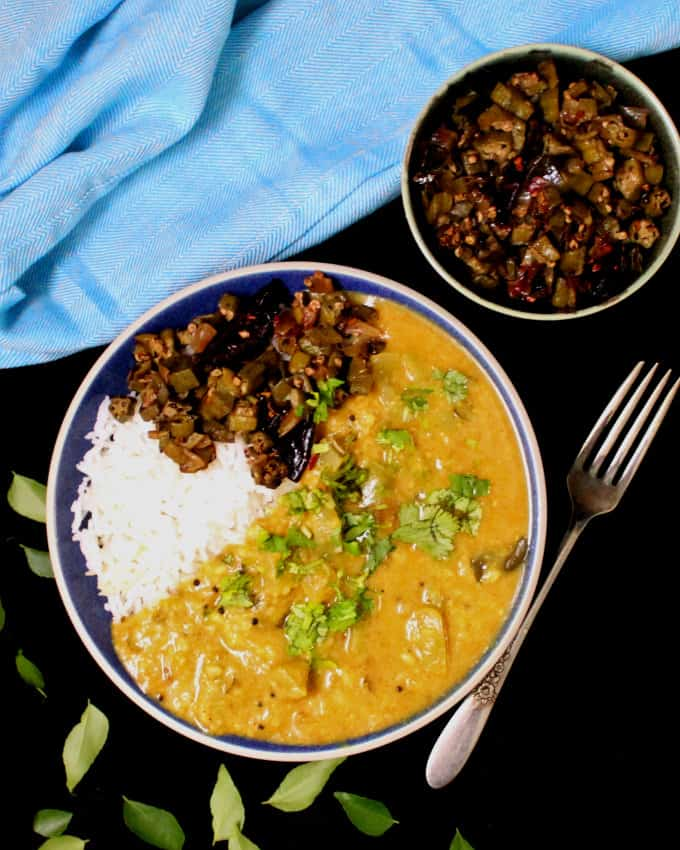 Green tomato dal in a bowl with rice and okra and a blue napkin behind with a fork and curry leaves strewn around
