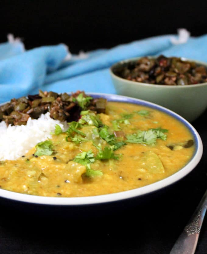 A front shot of the green tomato dal in a bowl with rice and okra and a blue napkin behind.
