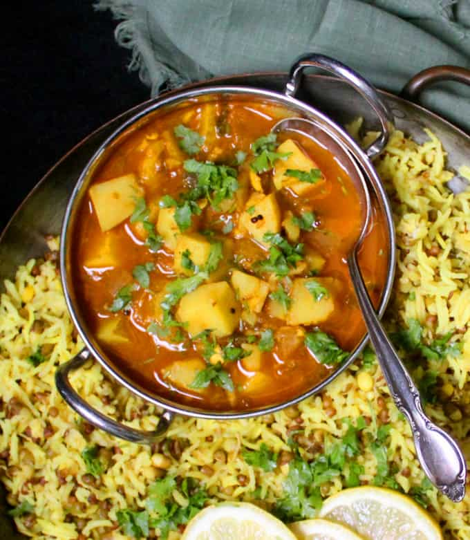 A steel karahi bowl with an easy spicy potato curry with a spoon in it, in a plate filled with moong khichdi and with lemon slices on the side.