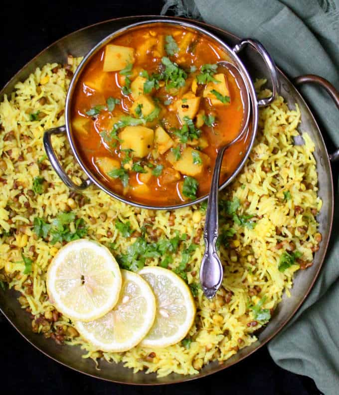 Top shot of Moong sprouts khichdi in a copper server with a kadhai bowl of spicy potato curry against a black background.