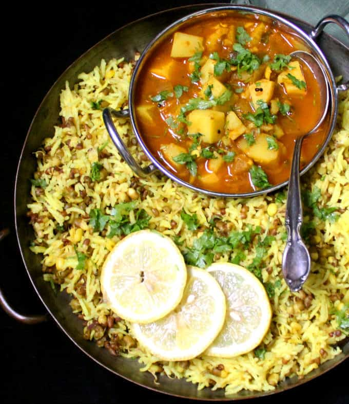 A copper serving tray filled with an Instant Pot Khichdi with Mung Bean Sprouts and a bowl with a red potato curry sits inside the server. Slices of lemon are to the side.