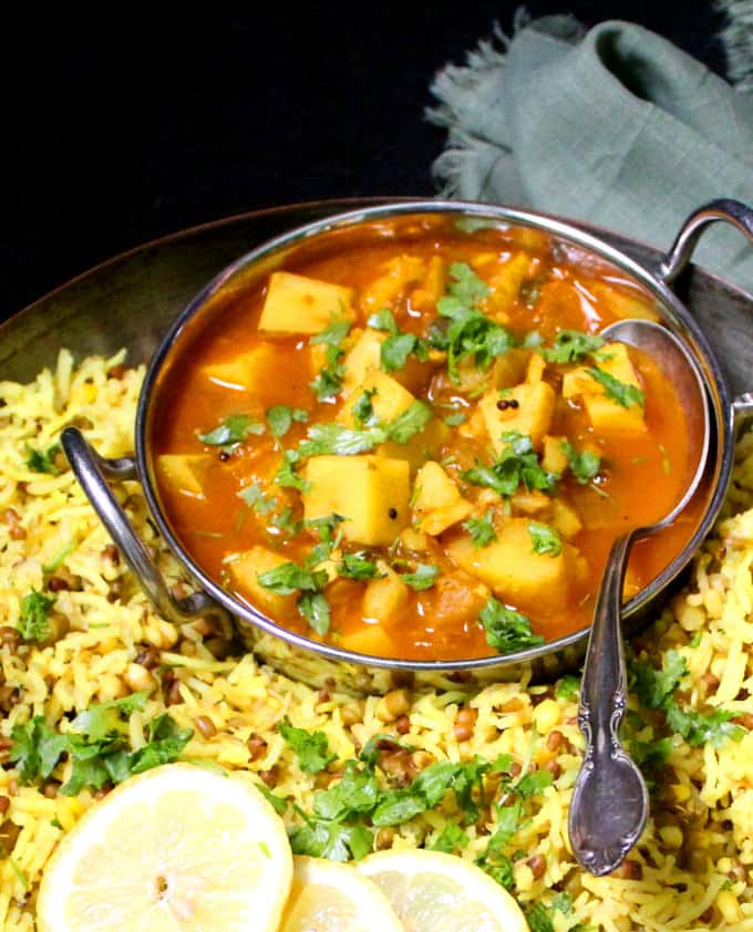 Front photo of a red, spicy Indian style potato curry with cilantro and served with khichdi.