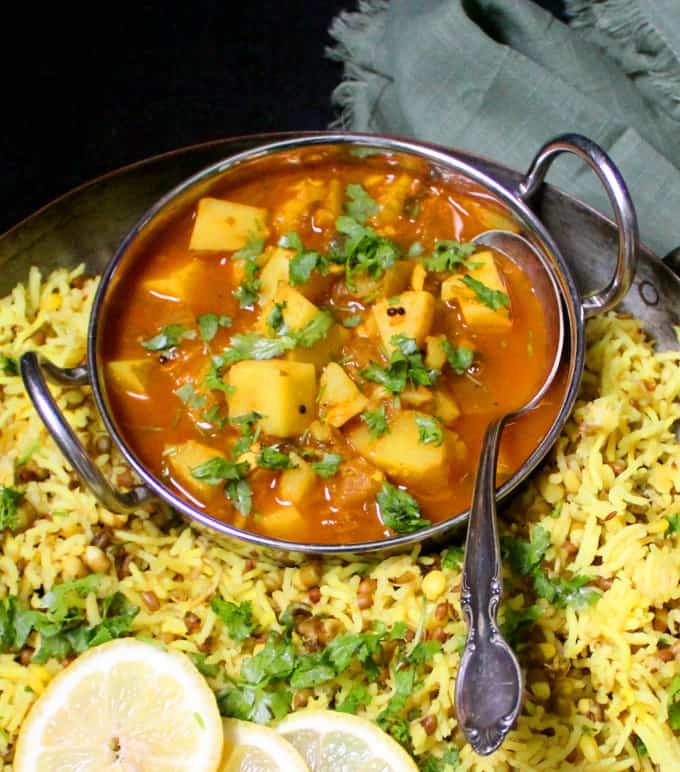 Frontal view of a red, spicy potato curry with pieces of potatoes and cilantro sprinkled on top in a larger copper server filled with mung bean khichdi.