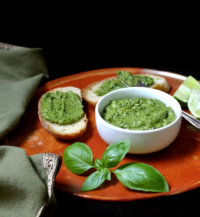 Basil pesto in a white bowl on an earthen plate surrounded by wedges of lime, fresh basil leaves, and slices of bread smeared with pesto for bruschettta.