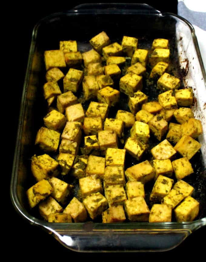 Baked tofu cubes in a glass baking dish.