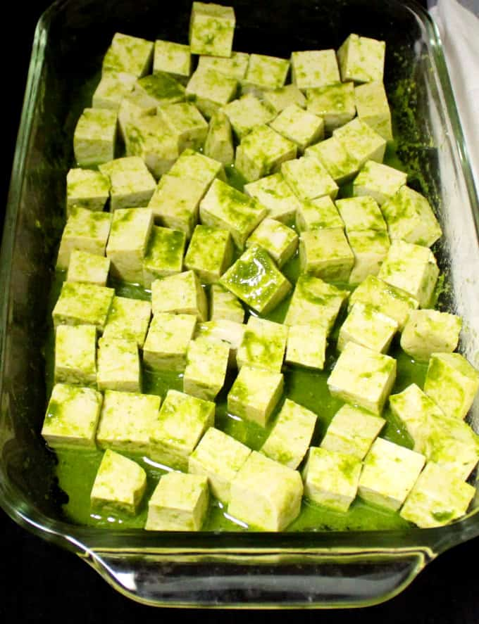 Tofu cubs soaking in the marinade in a glass baking dish.