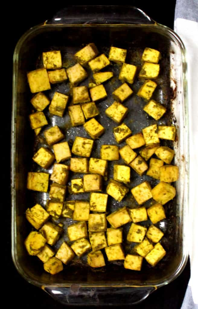 A top shot of a glass baking dish with cubes of marinated and baked tofu inside