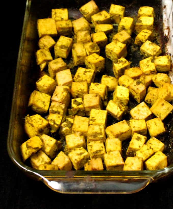 Photo of baked tofu cubes in a glass baking dish.