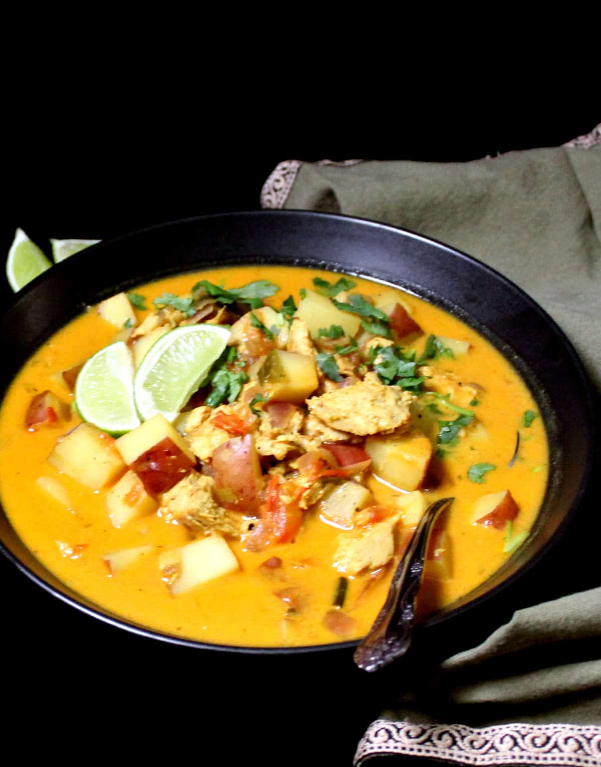 Front shot of vegan chickn curry with potatoes and slices of lime and cilantro.