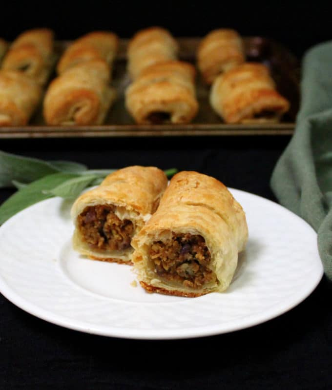 A sliced sausage roll on a white plate in the foreground with more sausage rolls on a baking sheet in the back against a black background