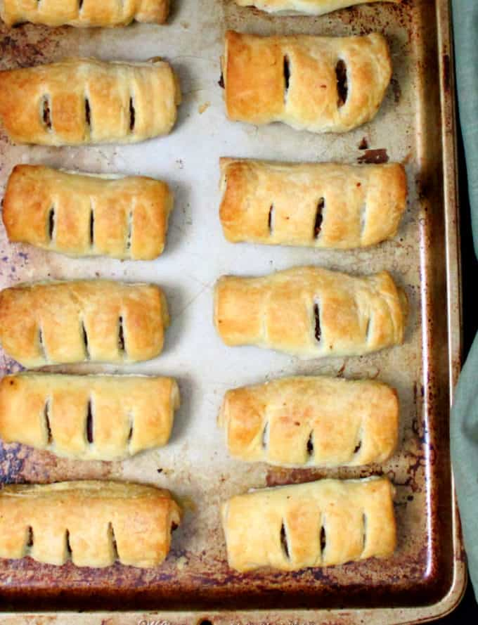 Baking sheet with twelve vegan sausage rolls in two rows