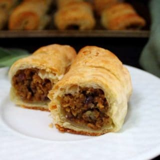 Golden, flaky vegan sausage rolls on a white plate stuffed with apple sage sausage and with more rolls in the background on a baking sheet