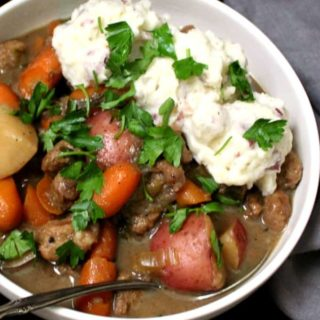 "A close shot of a hearty bowl of vegan Irish ""lamb"" stew with creamy mashed potatoes, carrots, celery and parsley"