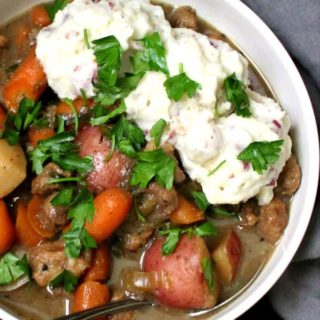 A close-up shot of a bowl of hearty Irish vegan stew with chunks of meaty soy, carrots, potatoes and mashed potatoes