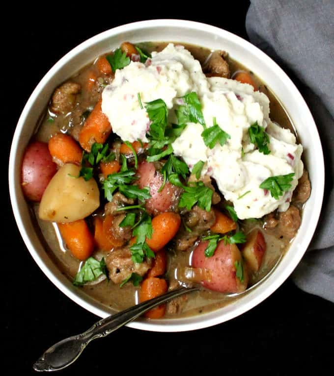 "A large white bowl with vegan Irish Stew with chunks of vegan soy ""lamb"", carrots, celery, potatoes, onions and herbs with creamy mashed potatoes on the side"