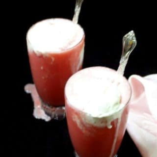 Two tall glasses of vegan watermelon smoothies topped with vanilla ice cream