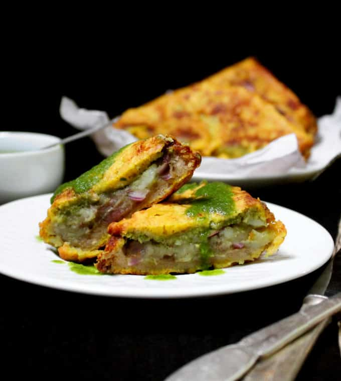 Bread pakora stuffed with potatoes, chaat masala and green and tamarind chutney on a white plate