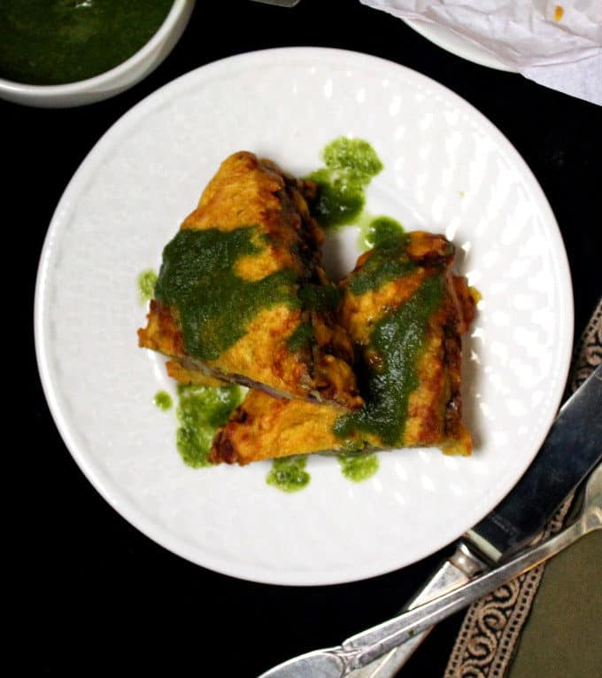 Two pieces of bread pakora smothered in green chutney on a white plate with a fork and knife next to it