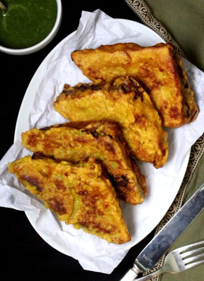 Four triangular bread pakoras on a white plate with green coriander chutney
