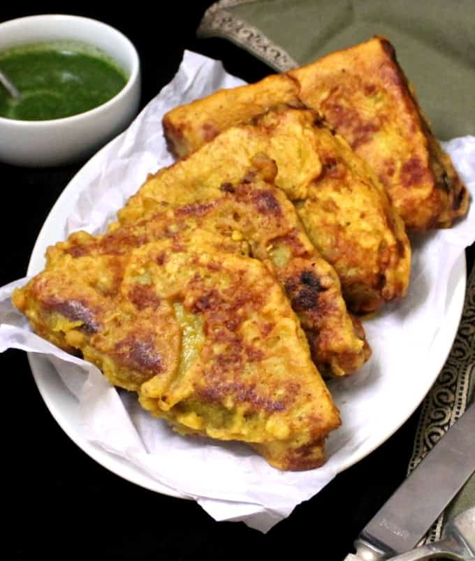 Four golden brown bread pakoras lined up on a white plate with green chutney in the background and a green napkin