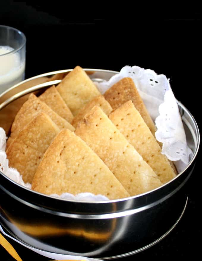 Classic vegan shortbread cookies in a tin with a white lace napkin