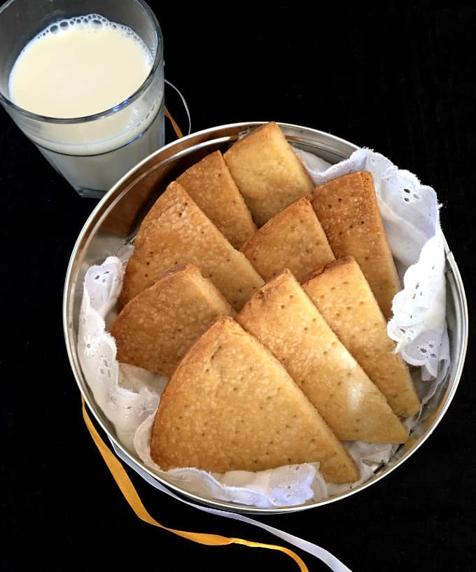 Top shot of a tin of vegan Scottish shortbread cookies nestled in a white lace napkin in a cookie tin with a glass of nondairy milk