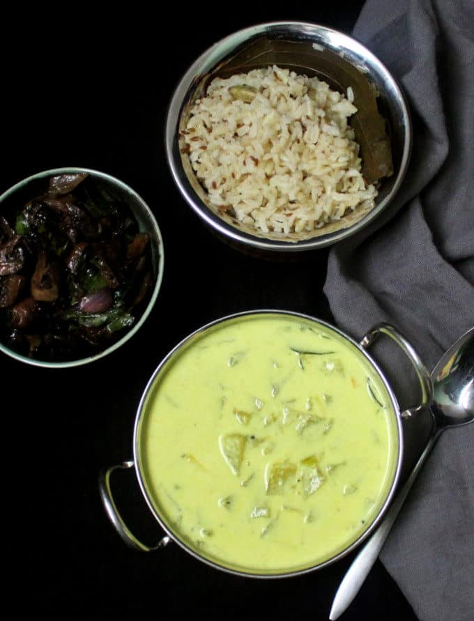 A dinner table set with creamy green tomato stew in a karahi bowl, brown jeera rice and mushroom stir-fry with a gray napkin on the side.