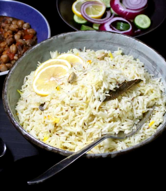 Front shot of a big bowl of jeera rice with cardamom and bay leaf and chana masala on the side